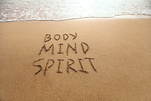body mina and spirit written on the sandy beach
