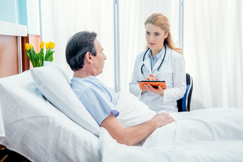 male patient laying in hospital bed with female doctor speaking to him