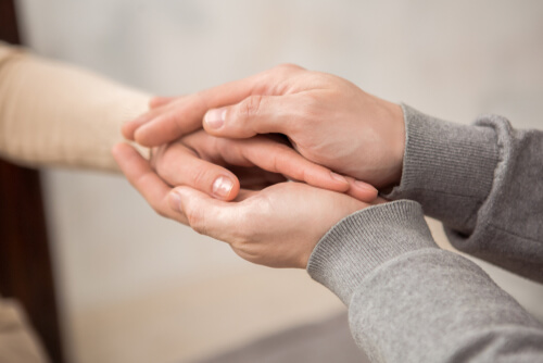 male therapist holding hand of the female patient with two hands supporting her psychologically