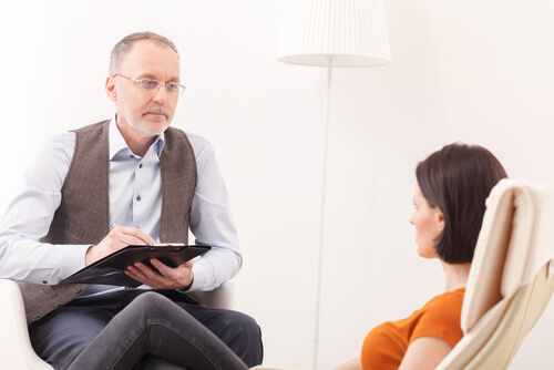 mature psychiatrist consulting a female patient in the office