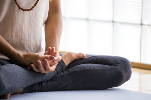 young woman meditating in the lotus pose indoors