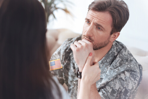 man in US military uniform speaking to a female therapist