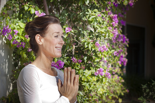 woman holding her hands together in namaste or praying in the beautiful blooming garden