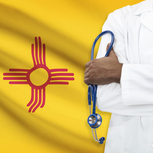 therapist with a stethoscope standing near the New Mexico state flag on the background