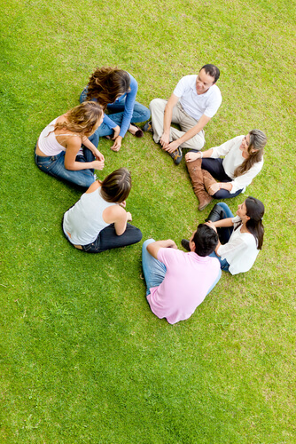 group of people sitting on the grass in the circle