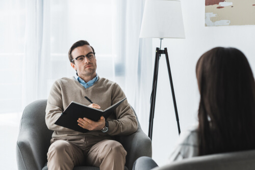 male therapist listening to a female patient in a light office