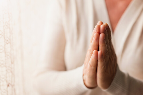 woman praying with folded hands