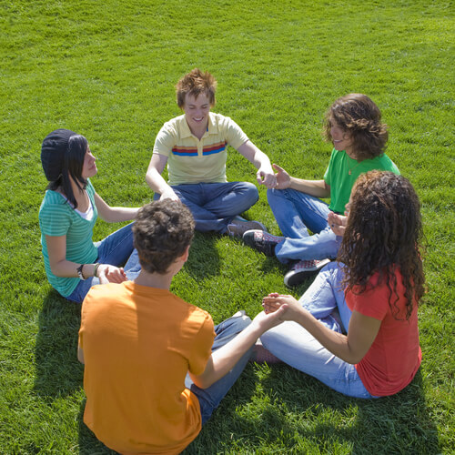 teens support group sitiing in the circle in park