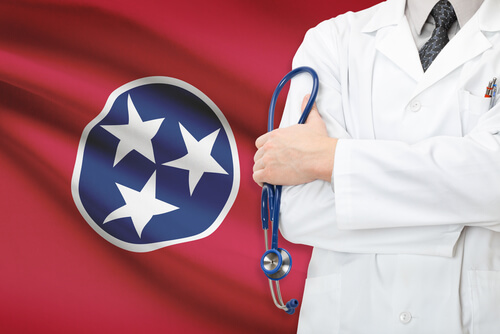 doctor in white uniform holding a stethoscope in hands with Tennessee flag on the background