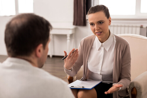 professional therapist gives advice to a male patient in her office