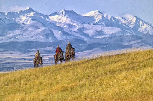 three men horseback riding with Montana mountain range on the background