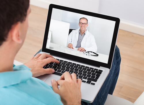 man having a videochat with doctor on the laptop at home