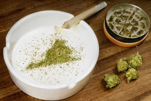 crumbled weed shaped as Virginia state in an ashtray and a joint