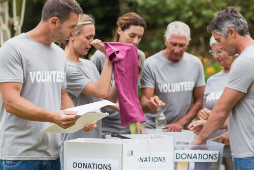 group of volunteers looking at the donation box with clothes