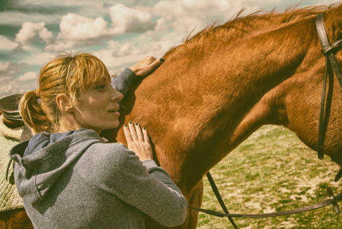 woman patting a horse neck