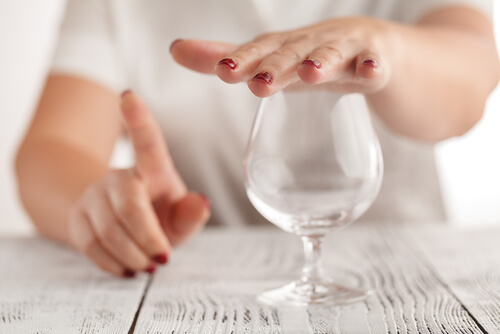 woman refuses to drink alcohol and covers the glass with hand so that noone can fill it