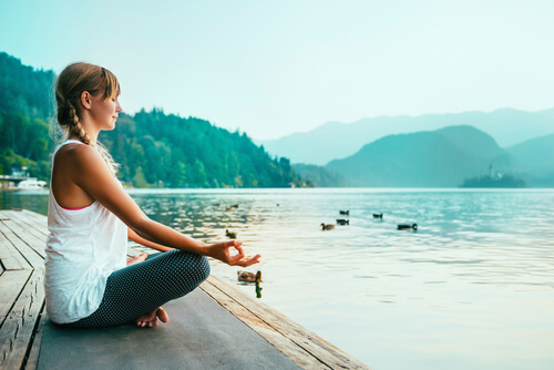 woman sitting in the lotus pose and meditating near the lake
