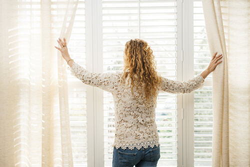 woman looking at the window with light curtains on the sunny street