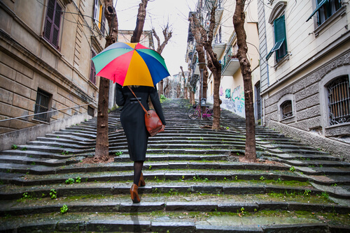 woman going upstairs outdoors holding a rainbow-colored umbrella