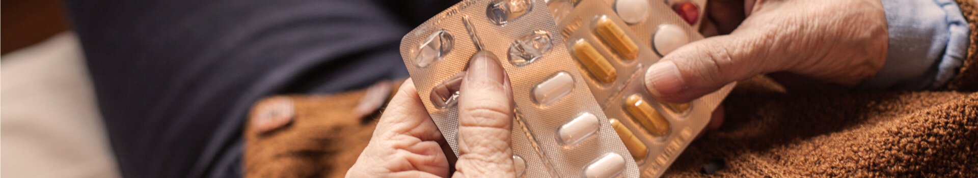 hands of a senior woman holding blisters with prescription medications