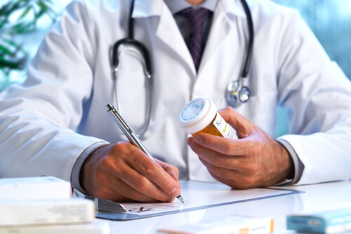 doctor writing out a prescription holding a bottle with pills in left hand