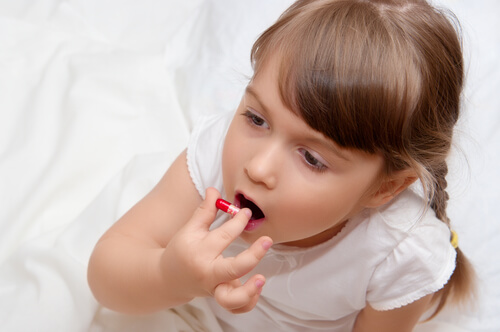little girl taking ADHD medication pill
