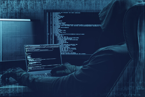 man in hood surfing dark web