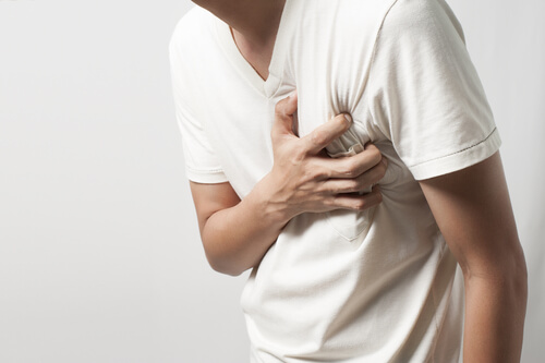 man holding chest because of pain