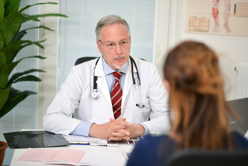 woman talking to a mature doctor in his office