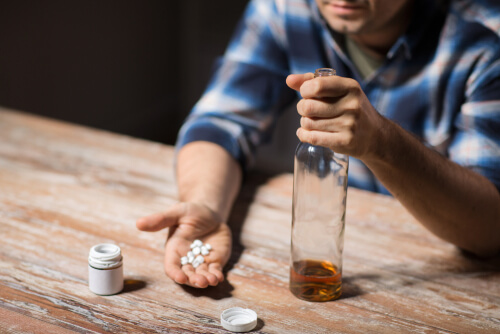 man with a bottle of alcohol and a handful of hydrocodone pills