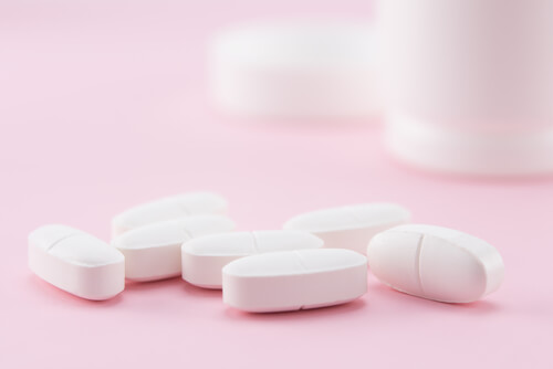 opioid painkiller pills on the pink background