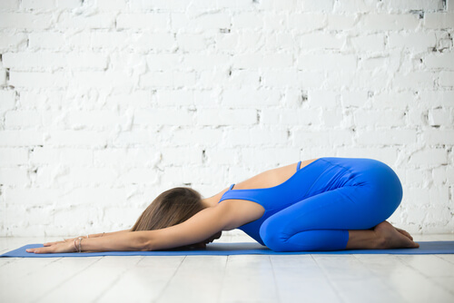 young woman in balasana yoga pose