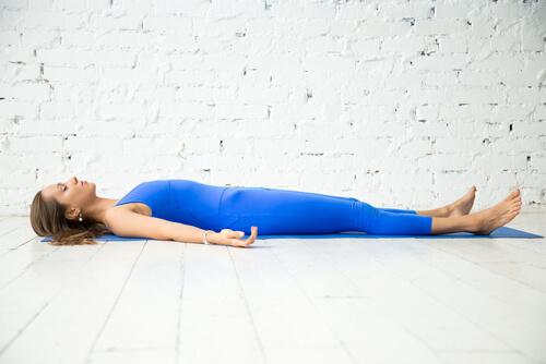 young woman in savasana yoga pose