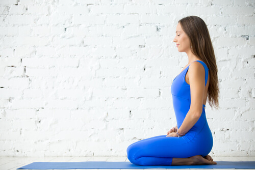 young woman sitting in vajrasana yoga pose