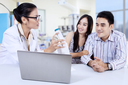 Asian female doctor with young couple in clinic