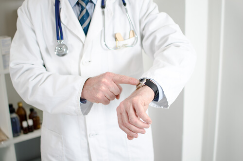 Doctor showing his watch with his finger