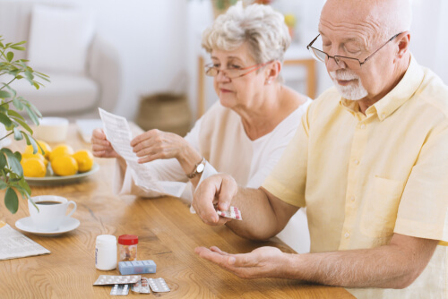 Senior man taking medication while his wife reading a prescription