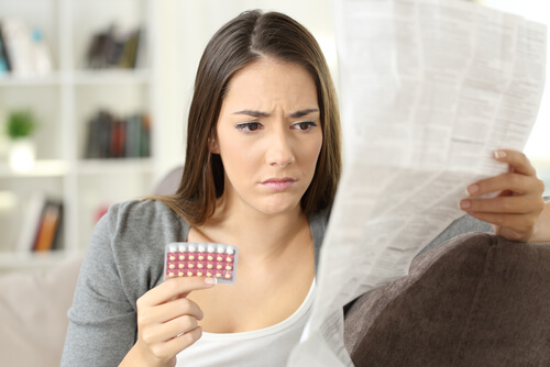 Worried woman reading pills warnings list