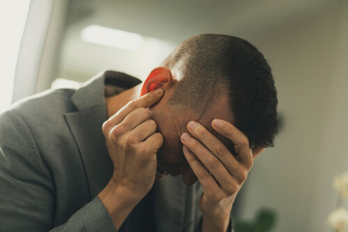 suffering man with one hand in his head