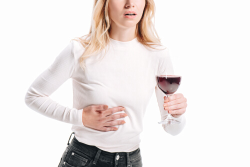 woman showing liver pain and holding glass of red wine