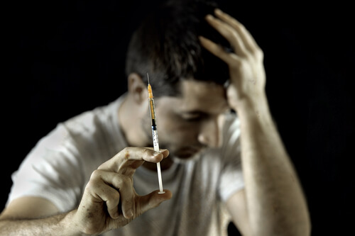 young man addicted to heroin holding syringe