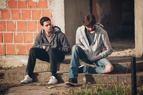 two young men sitting on the street