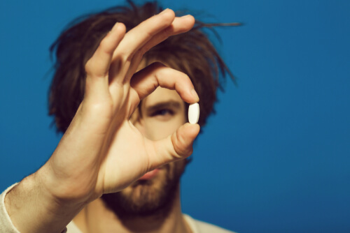 man holding antidepressant pill