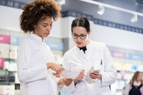 Two female pharmacists reading the information from Baclofen package