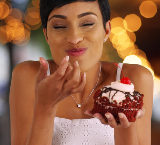 happy woman eating chocolate cupcake