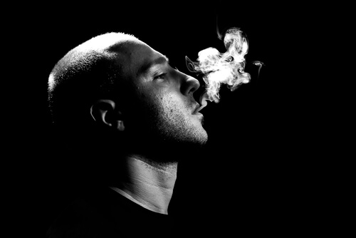 man exhaling the smoke