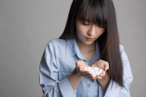 woman holding a many pills