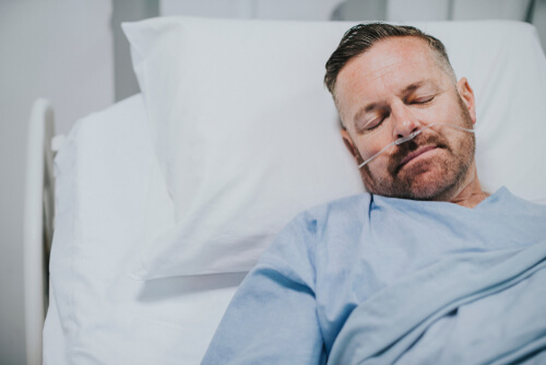 sick man in hospital bed with trouble breathing