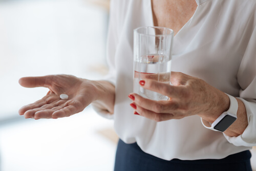 Meloxicam pill with a glass of water