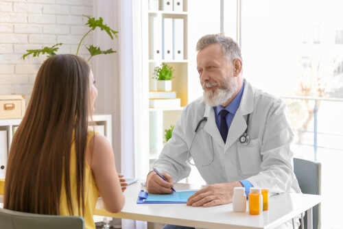Mature doctor consulting patient about meloxicam and ibuprofen safeness